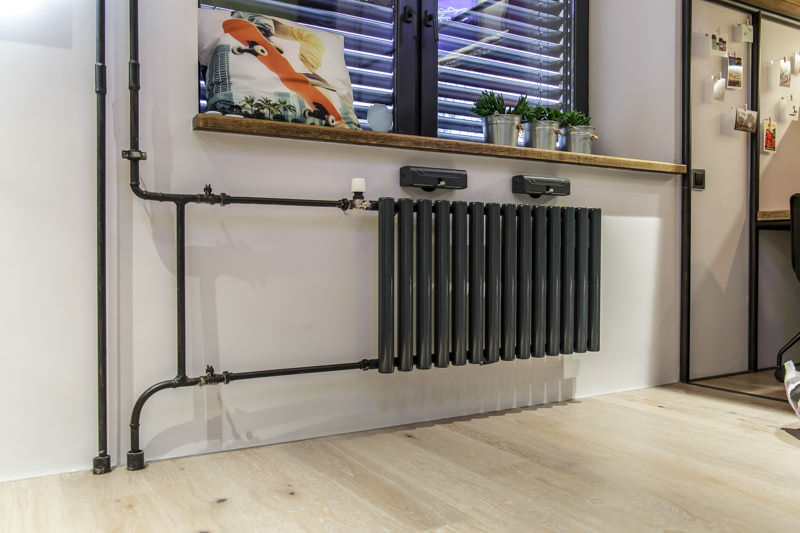 Black heating pipes on a white wall background