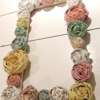 Papīra ziedi uz foto rāmja no koka