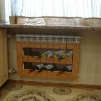 Painted heating radiator under shelves with wine bottles