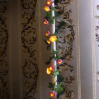 Garland with flowers on a heating pipe