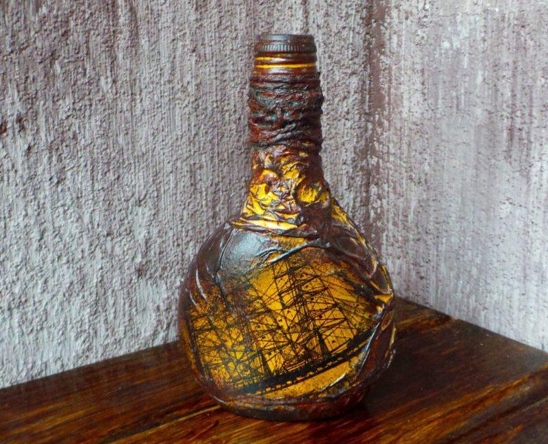 Buru laiva uz skaisti noformētas dāvanu pudeles