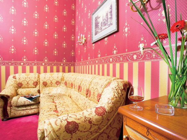 To give the room retro motifs, it is recommended that the lower part of the room be glued with wallpaper in a vertical strip, and the upper border is framed.
